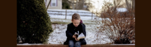 kid sitting on bench during winter